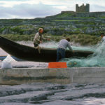 Aran Islands Fishermen gather their nets by their curraghs in Ireland