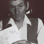 Michael Hartnett holds a poem he wrote to John B. Keane in Kiltimagh, Ireland, at an Aosdana meeting in 1995.